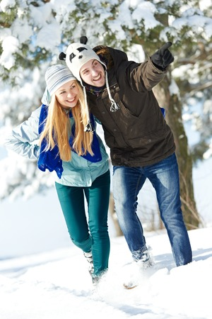 warm clothing: happy young smiling adult people in warm clothing at winter snow outdoors