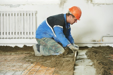 Plasterer at indoor concrete cement floor topping with float Stock Photo