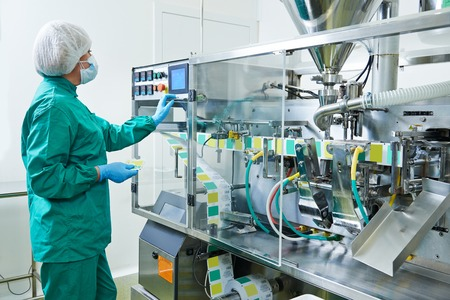 factory line: pharmaceutical factory woman worker operating production line at pharmacy industry manufacture factory Stock Photo