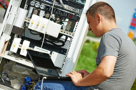 maintenance fitter: engineer working with laptop outdoors adjusting communication equipment in distribution box