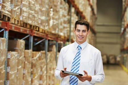 retail: male manager man worker standing in big modern warehouse with tablet computer