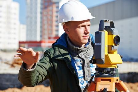 teodolito: Trabajador constructor Topógrafo con equipos de tránsito teodolito en el sitio de construcción al aire libre durante el trabajo de agrimensura Foto de archivo