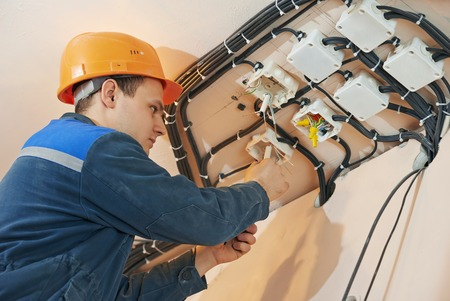 electrician engineer works with cables at distribution boxes in electric network Archivio Fotografico