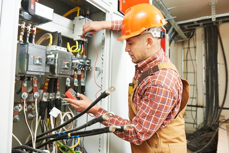 industrial industry: young adult electrician builder engineer worker in front of fuse switch board