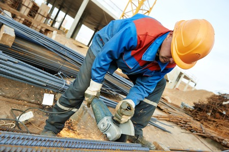 millwright: Construction builder worker with grinder machine cutting metal reinforcement rebar rods at building site