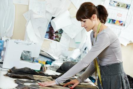 textile industry: retrato de joven trabajador sastre femenino de tela de tela en taller Foto de archivo