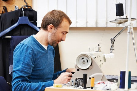 tailor measuring tape: male tailor working with sewing machine and cloth in workshop