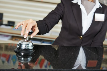 hotel worker: female receptionist worker ringing at hotel counter bell