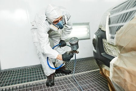 automobile repairman painter painting car body bumper in chamber 写真素材