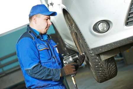 pneumatic: car mechanic screwing or unscrewing car wheel of lifted automobile by pneumatic wrench at repair service station