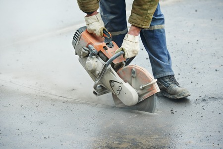 Builder worker with cut-off machine power tool breaking asphalt at road construction site photo