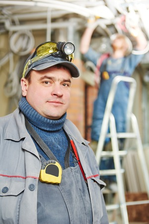 line electrician builder engineer worker at indoor construction site photo