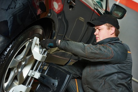 aligning: car mechanic installing sensor during suspension adjustment and automobile wheel alignment work at repair service station