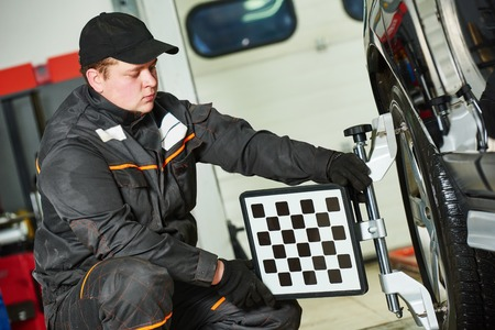 car mechanic installing sensor during suspension adjustment and automobile wheel alignment work at repair service station photo