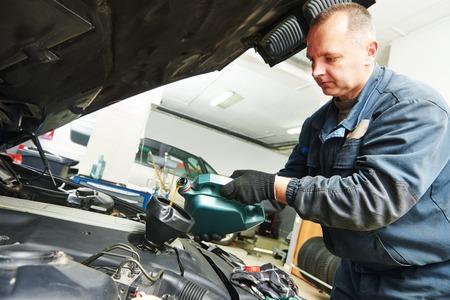mecanico: t�cnico mec�nico de autom�viles sustituci�n y verter el aceite de motor en el motor del autom�vil al mantenimiento de la estaci�n de servicio de reparaci�n Foto de archivo