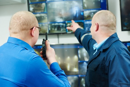 burglar: security executive chief discussing activity with worker in front of video monitoring surveillance security system Stock Photo