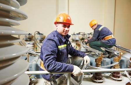 electricidad industrial: Electricistas trabajador del reparador liniero en enorme poder transformador de los trabajos de instalaci�n industrial Foto de archivo