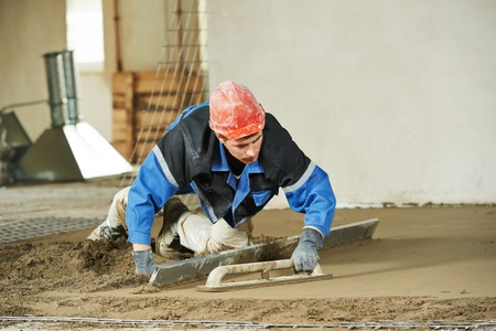 concrete construction: Plasterer at indoor concrete cement floor topping with float Stock Photo