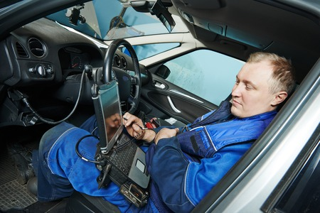 diagnosing: automobile computer diagnosis auto repairman industry mechanic worker servicing car auto in repair or maintenance shop service station