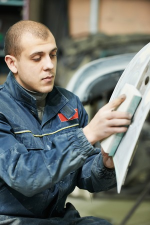auto mechanic worker sanding polishing bumper car at automobile repair and renew service station shop by sandpaper photo