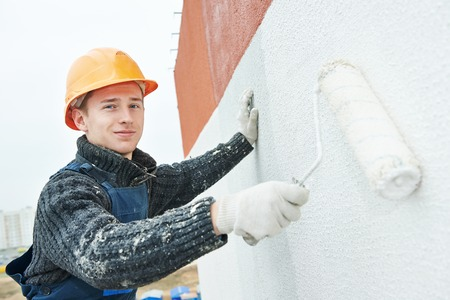 plasterer: builder worker painting facade of high-rise building with roller