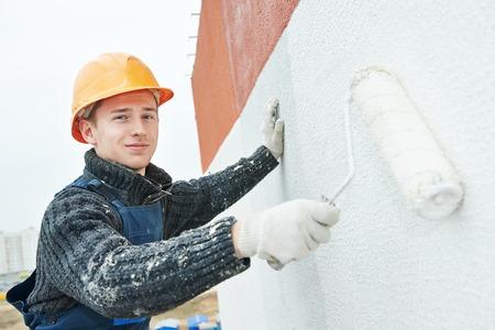 builder: fachada de pintura de trabajador de generador de rascacielos edificio con rodillos  Foto de archivo