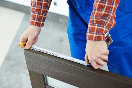 carpintero: Primer plano carpintero manos con cinta de medida durante el proceso de instalaci�n de la puerta de madera