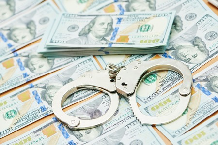 extortion: money bribe or corruption theme. handcuffs lying on dollars banknotes