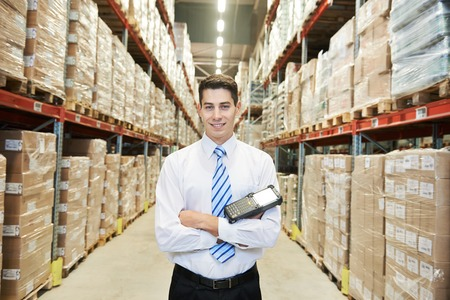 distribution: male manager man worker standing in big modern warehouse