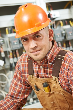 high voltage current: young adult electrician builder engineer worker in front of fuse switch board