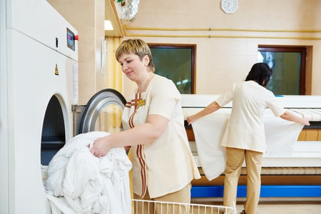 laundry: Hotel linen cleaning services. Woman operating with industrial washing machine