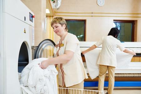personal de limpieza: Servicios de limpieza de la ropa de hotel. Mujer que opera con lavadora industrial