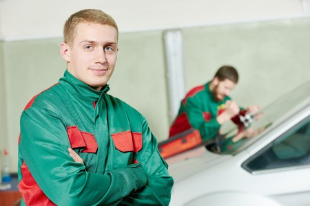 glazier: Automobile glazier repairman portrait in front of worker repairing car windscreen in auto service station garage Stock Photo
