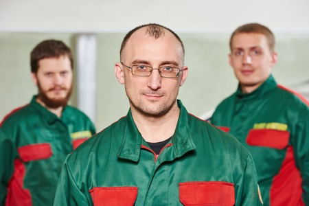 glasscutter: Group portrait of service repairman in uniform in automobile service station garage Stock Photo