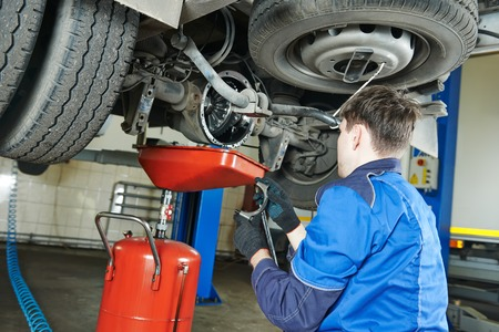 vehicle part: auto repairman mechanic works with rear axle reduction gear of commercial van in car auto repair or maintenance shop service station