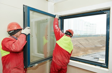 replacement: Two male industrial builders workers at window installation