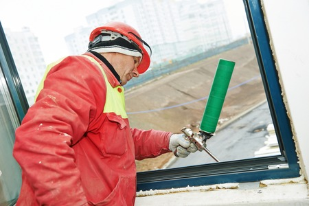 construction builder works with polyurethane foam during frame insulation at window installation Stock Photo
