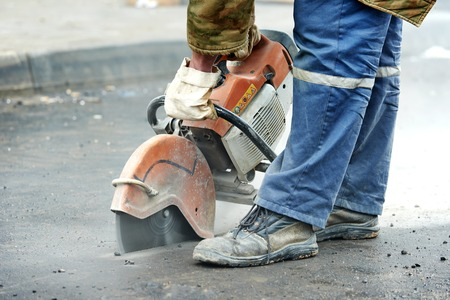 jack tar: Builder worker with cut-off machine power tool breaking asphalt at road construction site
