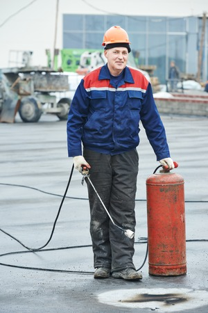 tar felt: Roofer installer worker portrait at roofing felt with heating and melting of bitumen roll by torch on flame during roof repair