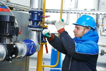 industrial heat engineer worker plumber at boiler room installation Foto de archivo