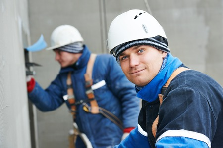 builders at facade plastering work during industrial building with putty knife float Stockfoto