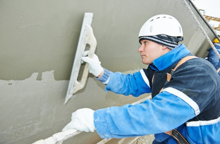 builder at facade plastering work during industrial building with putty knife float Stock Photo - 36933514
