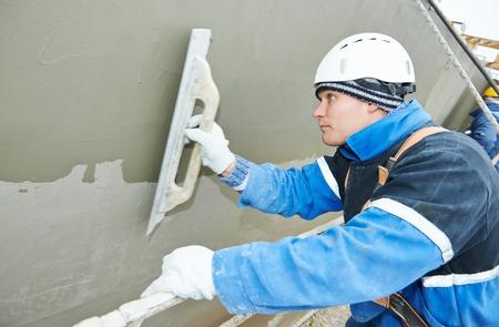 facade: constructor en el trabajo de enyesado fachada durante edificio industrial con una esp�tula flotador Foto de archivo