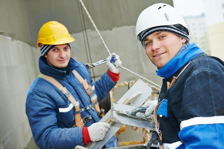 steeplejack: builders at facade plastering work during industrial building with putty knife float Stock Photo