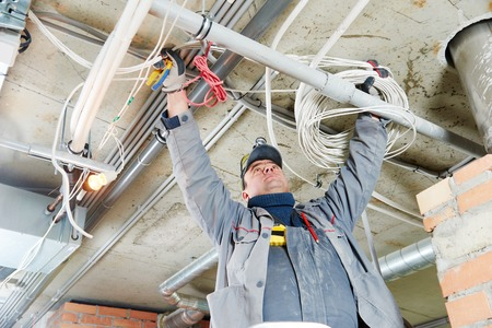 line electrician builder engineer worker at indoor construction site cabling 스톡 콘텐츠
