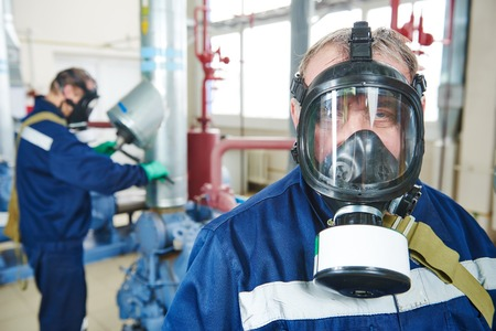 chiller: portrait of service engineer worker with gas mask at industrial compressor station for refrigeration or ammoniac chiller system at factory