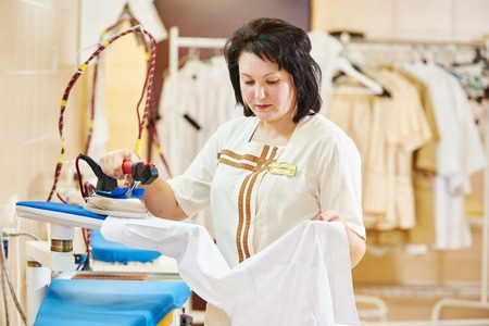 dry cleaner: cleaning services. Woman with iron working at ironing shop Stock Photo