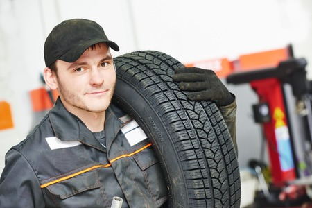 tire fitting: repairman mechanic portrait in car auto repair or maintenance shop service station with automobile wheel tire