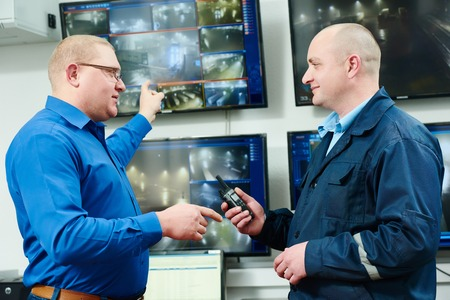 security monitoring: security executive chief discussing activity with worker in front of video monitoring surveillance security system Stock Photo