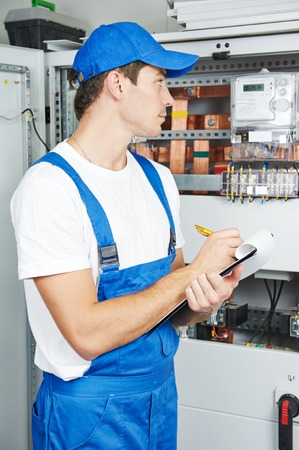 data distribution: Young adult electrician builder engineer inspecting electric counter equipment in distribution fuse box